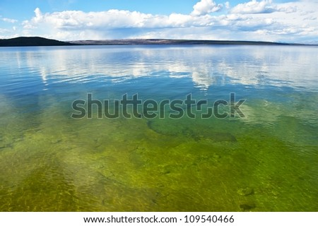 Calm Lake Yellowstone Scenery. Wyoming, USA. Crystal Clear Yellowstone Lake Waters. Nature Photo Collection. - stock photo
