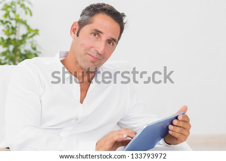 Calm man with his digital tablet in the living room