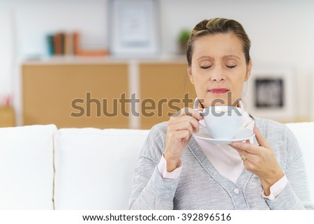 Calm mature female with closed eyes enjoying the fragrance of hot coffee in mug held up to her nose while sitting on sofa