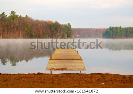 Calm morning on an Adirondack lake the dock stretches from the shore - stock photo