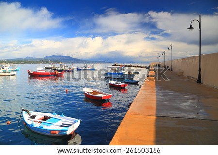Calm morning with small fishing boats along protective pier in the harbor of Koroni, Greece - stock photo