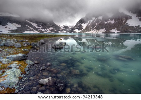Calm Mountain Lake under low clouds - stock photo