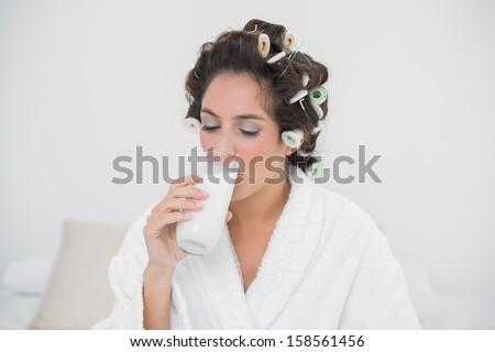 Calm natural brunette drinking glass of milk in bedroom - stock photo
