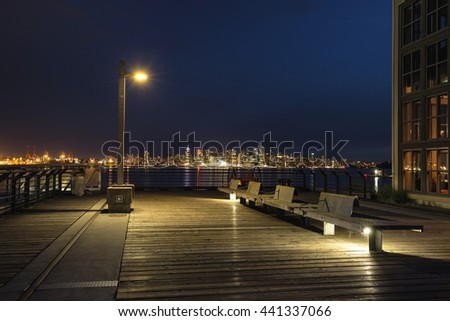 Calm Night Scene at Lonsdale Quay with Downtown Vancouver in the background. Taken after a cloudy sunset. - stock photo