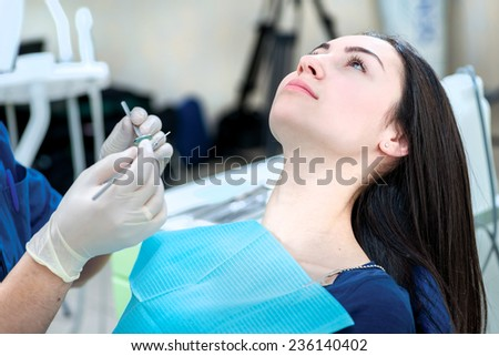 Calm patient sitting in a dentist chair. The patient is sitting in the dentist's dental chair while the dentist is going to check the health of her teeth - stock photo