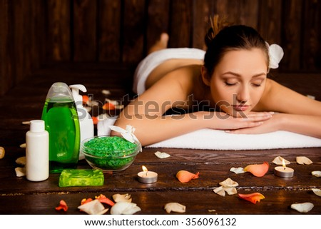 Calm pretty young woman laying in spa salon with closed eyes and relaxed - stock photo