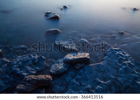 Calm rocky shore of the Baltic sea at night, moon light. Long exposure shot. - stock photo