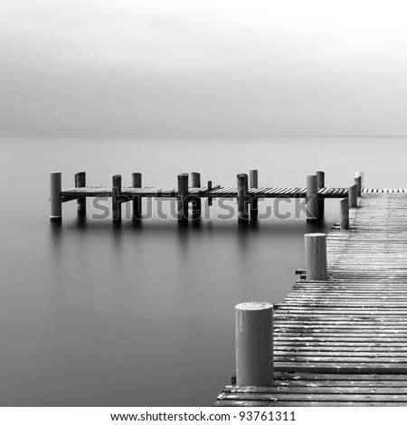 Calm scene in black and white with detail of wooden jetty - stock photo