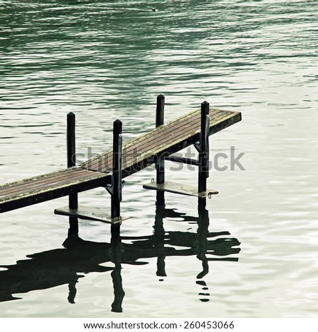Calm scene with old wooden jetty at Lake Geneva, Switzerland. Square toned image, instagram effect - stock photo