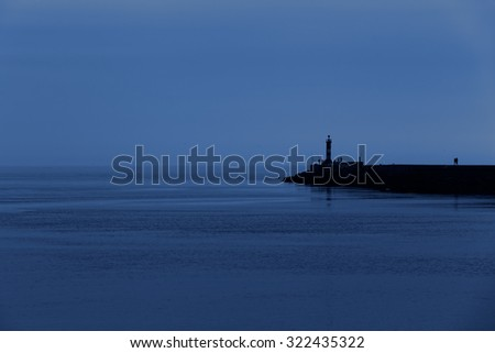 Calm sea dusk at the pier of the Ave river mouth harbor, Vila do Conde, Portugal - stock photo