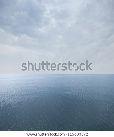 calm sea with cloudy sky at the horizon - stock photo