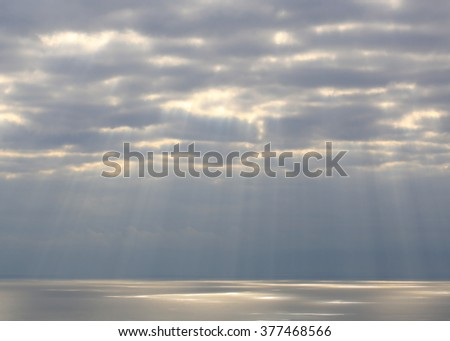 Calm seascape with stormy sky where sun-rays get through the clouds. - stock photo