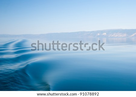 Calm surface of lake Baikal with trace of the ship - stock photo
