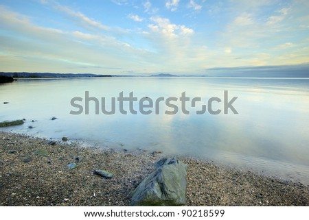 calm water in the Bay with blue sky's and clouds reflecting off the water rock on the shore - stock photo