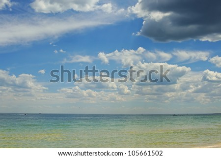 Calm water on sandy beach in summer with blue sky and clouds, people on boats on horizon and and dark cloud in corner - stock photo