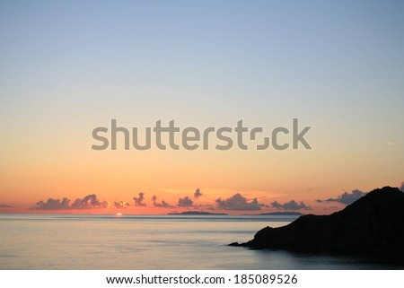 Calm water with rocks on the right and clouds along the horizon. - stock photo