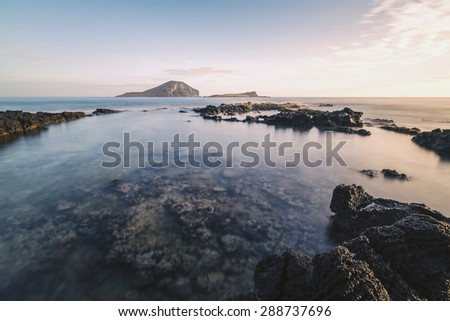 Calm waters of a tide pool off the east coast of Oahu, Hawaii during sunrise with two islands on the horizon - stock photo