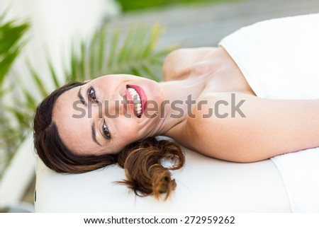 Calm woman lying on massage table in the health spa - stock photo