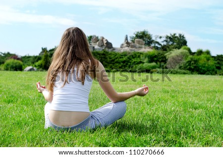 Calm woman meditates on beautiful green lawn