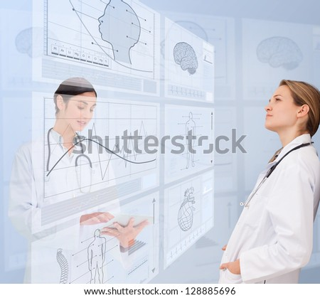 Calm women doctors using futuristic interfaces - stock photo