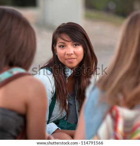 Calm young Native American teenager between two friends