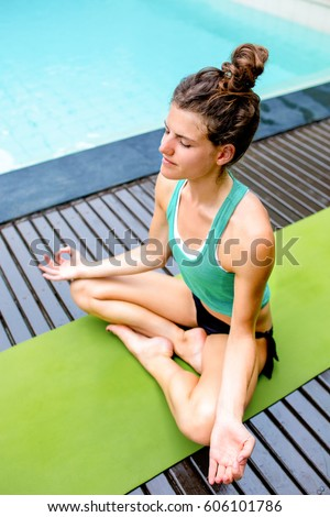Calm young woman crossing legs during meditation