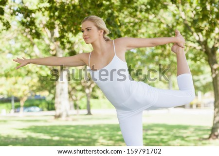 Calm young woman doing yoga standing in a park spreading her arms - stock photo
