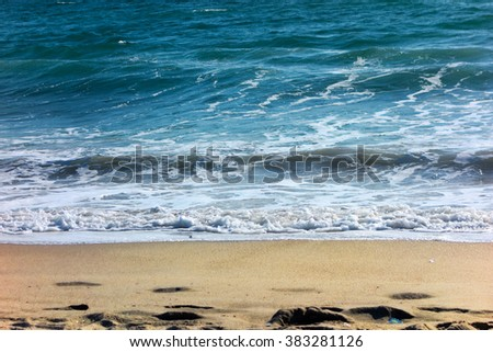 Calming background of wet yellow sand with footprints and rolling dark blue waves on ocean side beach in Southern California