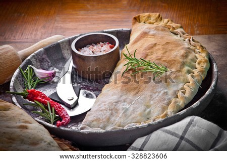 Calzone, closed pizza, Italian pastry stuffed with cheese, meat - stock photo