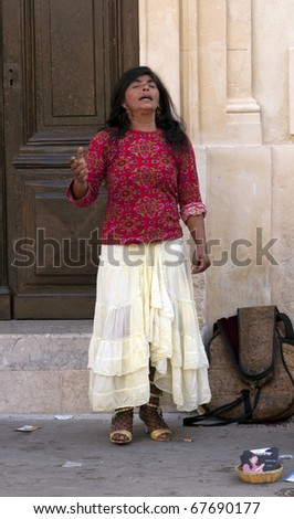 CAMARGUE,FRANCE, MAY 2007: Unidentified gypsy woman sings on street during the yearly gypsy pilgrimage to honor their patron Saint Marie Sarah on May 20, 2007, Saintes Maries de la Mer, France. - stock photo