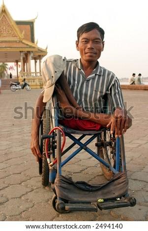 Cambodian man in a wheelchair. - stock photo