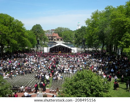 CAMBRIDGE, MA - MAY 29: People sit in chairs as Harvard Business Students of Harvard University gather for their graduation ceremony on Commencement Day on May 29, 2014 in Cambridge, MA. - stock photo