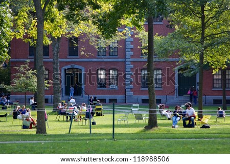 CAMBRIDGE, MA, USA - SEPTEMBER 27: Students and tourists rest in lawn chairs in Harvard Yard, the open old heart of Harvard University campus on September 27, 2012 in Cambridge, MA, USA. - stock photo