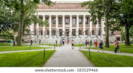 CAMBRIDGE, USA - JULY 12: View of the campus of the famous Harvard University in Cambridge, Massachusetts, USA with some students, locals, and tourists passing by on July 12, 2013. - stock photo