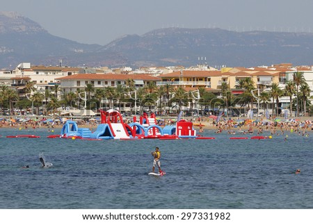 CAMBRILS, SPAIN - JULY 12, 2015: People having fun on the beach in a hot sunny day on July 12, 2015 at the beach of Cambrils in Catalonia, Spain, a famous summer destination