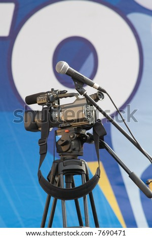 Camcorder with microphone on tripod - stock photo