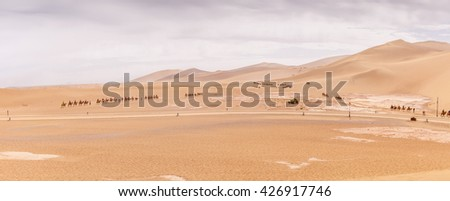 Camel caravans in the Mingsha Shan desert in the Moon Lake park, Dunhuang city, Gansu Province, Western China. - stock photo