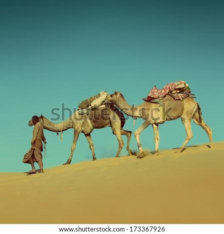 cameleer in desert on sand dune - vintage retro style - stock photo