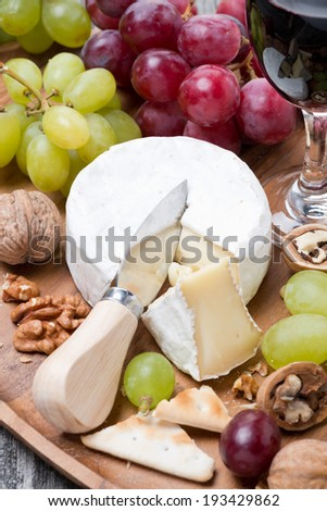 Camembert, a glass of red wine, grapes and crackers, vertical