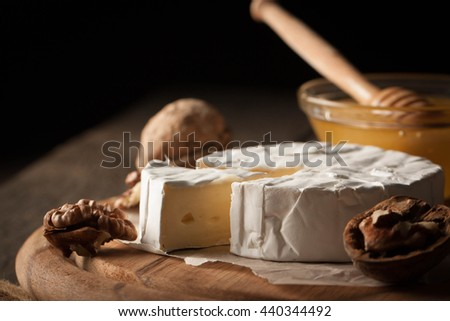 Camembert and brie cheese on wooden background with nuts spices and garlic. Italian food. Dairy products.