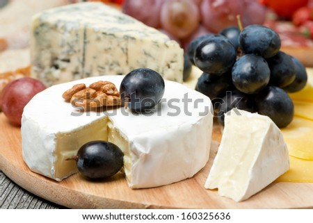 Camembert, blue cheese, grapes and walnuts, close-up - stock photo