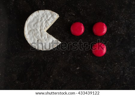 Camembert cheese and mini pieces on black background arranged in pac-man style. Funny game with food, traditional French dish for wine on lunch and dinner closeup. - stock photo