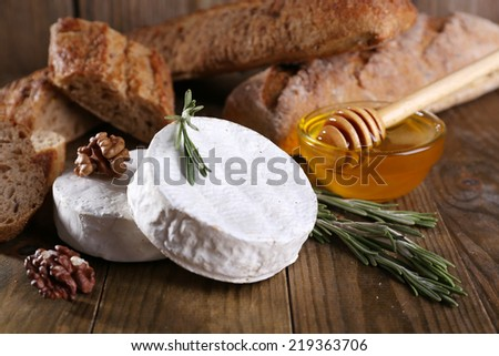 Camembert cheese on plate, honey, nuts and bread on wooden background