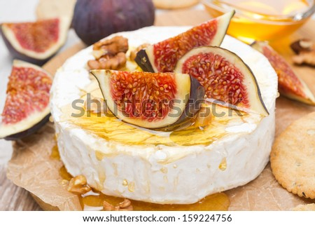 Camembert cheese with honey, figs, walnuts and crackers on a wooden board, close-up, horizontal - stock photo
