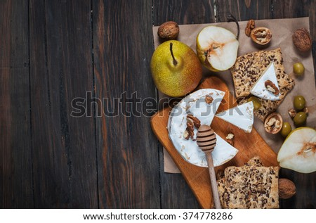 Camembert cheese with walnuts, honey and pears on rustic table. Glass of white wine. - stock photo