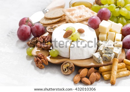 camembert, grapes and snacks on a white table, closeup, horizontal