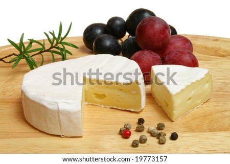 Camembert - soft cheese served on a wooden board with pepper, grapes and rosemary