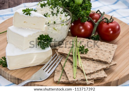Camembert with Crispbread and Herbs on a cutting board