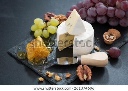 Camembert with fresh honey, grapes and nuts on dark background, horizontal, close-up - stock photo