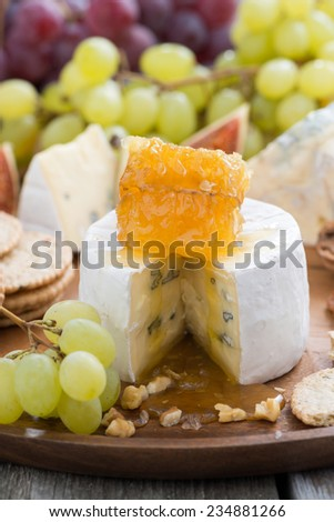 camembert with honey and fruit close-up on a wooden tray, vertical, close-up